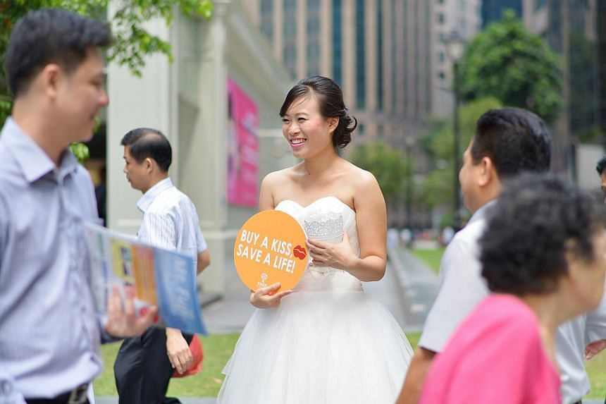 """Ms Kwa Mee Ling, 20, a Singapore Management University student, was one of the """"brides"""" at Raffles Place yesterday asking people for cash donations for the Bone Marrow Donor Programme or to sign up as donors. Those who made donations were given a Her"""