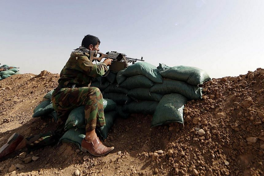 Members of Kurdish Peshmerga forces hold their position on June 21, 2014, in the Iraqi village of Basheer, 15 kilometers south of the city of Kirkuk, overlooking locations under Sunni militants led by the Islamic State of Iraq and the Levant (ISIL).