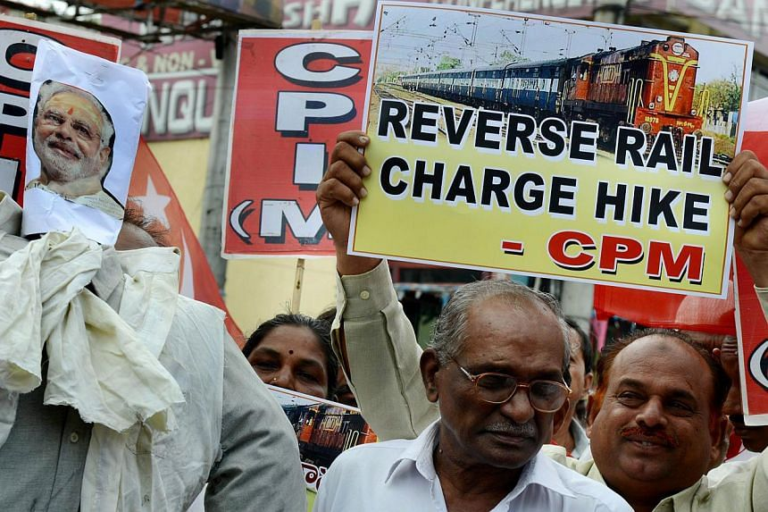 Indian activists of the Communist Party of India-Marxists (CPI-M) holding placards and an effigy representing Prime Minister Narendra Modi during their protest against the price hike in railway fares, in Hyderabad on June 21, 2014. -- FILE PHOTO: AFP