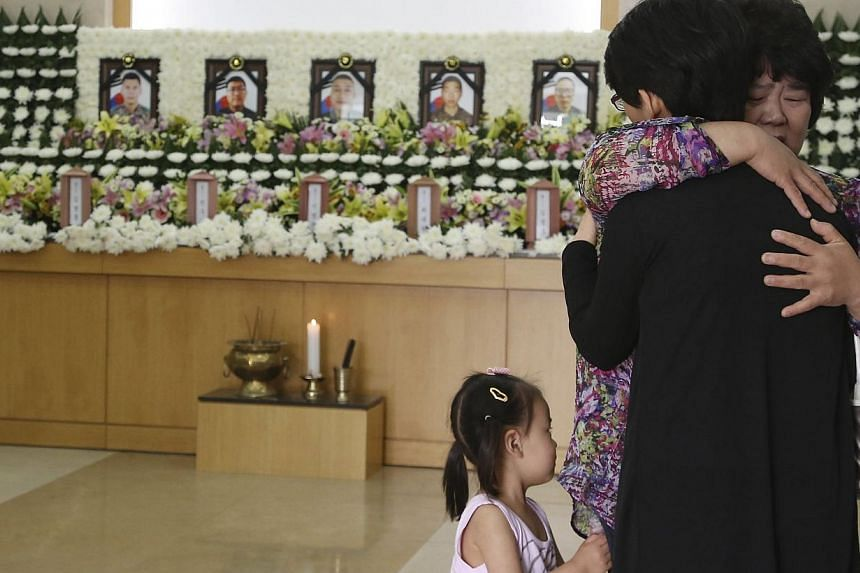 A mourner comforts a relative of a dead soldier on June 23, 2014after paying her tribute at the group memorial altar of the five soldiers who were killed by a conscript soldier, identified as Sergeant Lim. -- PHOTO: REUTERS