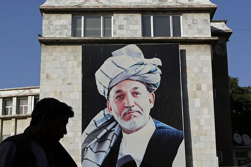 People walk past a picture of Afghan President Hamid Karzai on a street in Kabul on June 26, 2014.The Afghan president may not have signed a key measure aimed at clamping down on the financing of terrorism, reviving concern the country's banks