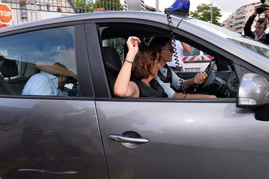 Wojciech Janowski, son-in-law of Monaco heiress Helene Pastor, hidden by the arm of a policeman, leaves a police station in a police car during a transfer from Nice to the courthouse in Marseille on June 27, 2014.The son-in-law of the 77-year-o