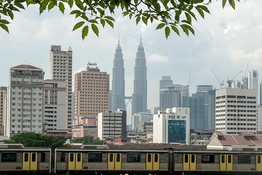 A Light Rail Transit (LRT) train travels along the tracks as Malaysia's iconic Petronas Twin Towers loom in the backgrond in downtown Kuala Lumpur on May 29, 2014.Malaysia's economy is expected to expand 5.4 per ent this year, picking up from