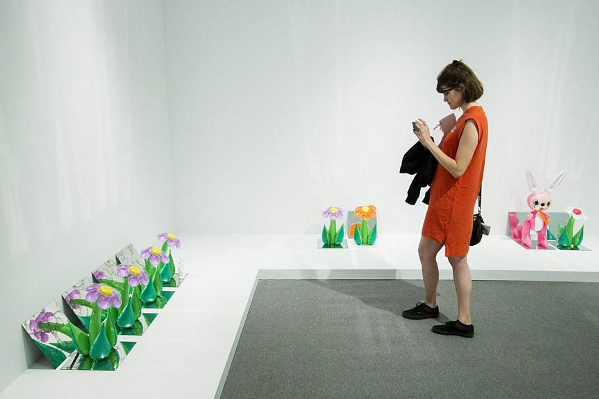 A woman takes photographs of the series Inflatables during a media preview before the opening of a Jeff Koons retrospective at the Whitney Museum of American Art in New York on June 24, 2014. -- PHOTO: REUTERS