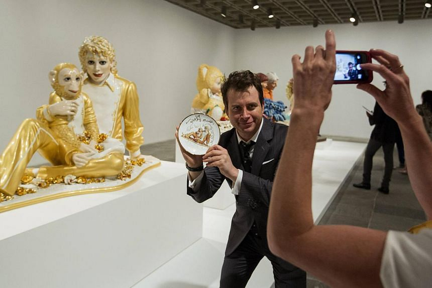A man holds a signed plate with the likeness of the sculpture Michael Jackson and Bubbles in front of the actual sculpture during a press preview before the opening of a Jeff Koons retrospective at the Whitney Museum of American Art in New York on Ju