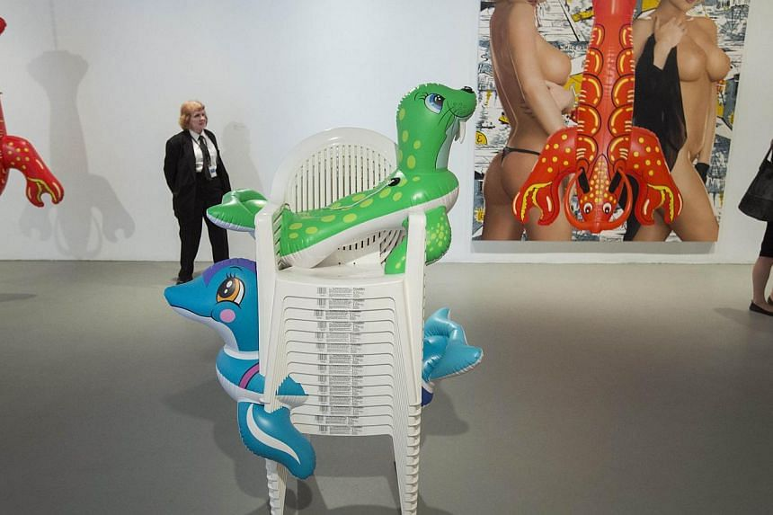 A security guard stands in front of sculptures Lobster (left) and Seal Walrus (Chairs) (centre) and the painting Elvis during a press preview before the opening of a Jeff Koons retrospective at the Whitney Museum of American Art in New York on June 2