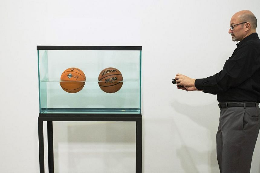 A man photographs the sculpture Two Ball 50/50 Tank during a media preview before the opening of a Jeff Koons retrospective at the Whitney Museum of American Art in New York on June 24, 2014. -- PHOTO: REUTERS