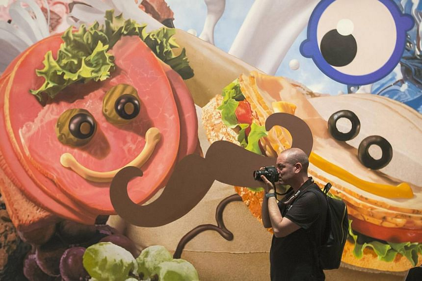 A man takes pictures in front of the painting Sandwiches during a press preview before the opening of a Jeff Koons retrospective at the Whitney Museum of American Art in New York on June 24, 2014. -- PHOTO: REUTERS