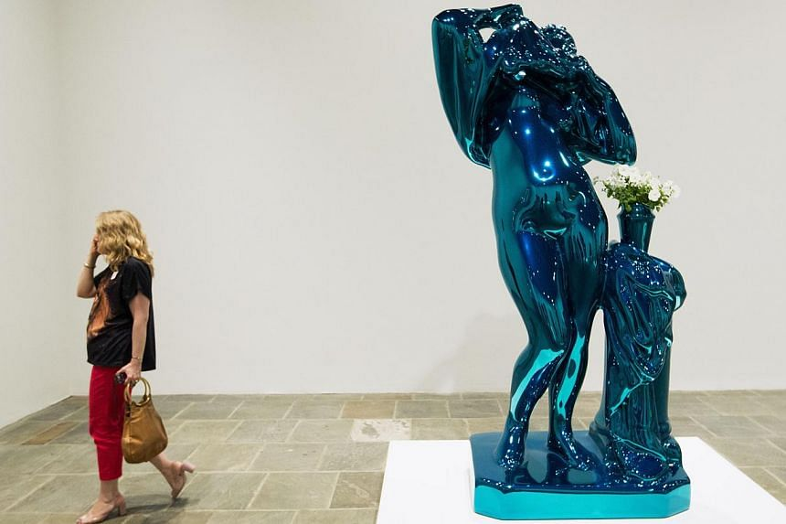 A woman walks past the sculpture Metallic Venus during a press preview before the opening of a Jeff Koons retrospective at the Whitney Museum of American Art in New York on June 24, 2014. -- PHOTO: REUTERS