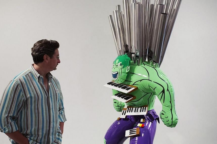A man inspects the sculpture Hulk (Organ) during a press preview before the opening of a Jeff Koons retrospective at the Whitney Museum of American Art in New York on June 24, 2014. -- PHOTO: REUTERS