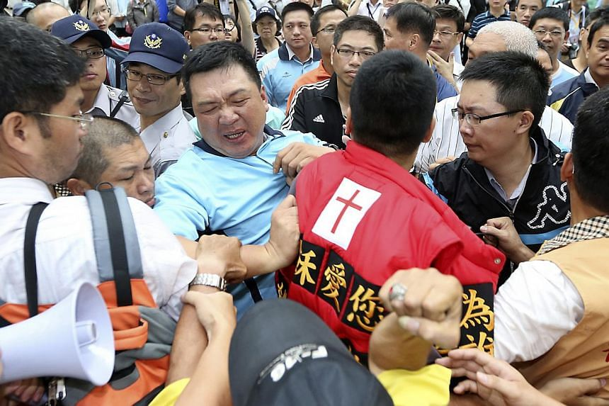Pro-democracy activists (in red and orange vests) scuffle with police officers (in black and blue shirts) as Mr Zhang Zhijun, director of China's Taiwan Affairs Office, arrives in Kaohsiung, southern Taiwan, on June 27, 2014. -- PHOTO: REUTERS