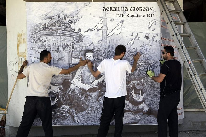 People put up a poster of Gavrilo Princip, the 19-year-old Bosnian Serb who gunned down Archduke Franz Ferdinand in 1914 and lit the fuse for World War One, in Bosansko Grahovo, next to Princip's birth village in Obljaj on June 27, 2014. -- PHOTO: RE