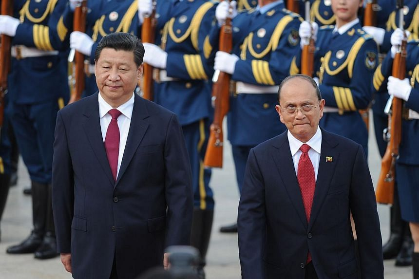 Myanmar President U Thein Sein (right) and Chinese President Xi Jinping (left) inspect Chinese honour guards during a welcome ceremony outside the Great Hall of the People in Beijing on June 27, 2014.Chinese President Xi Jinping feted neighbour