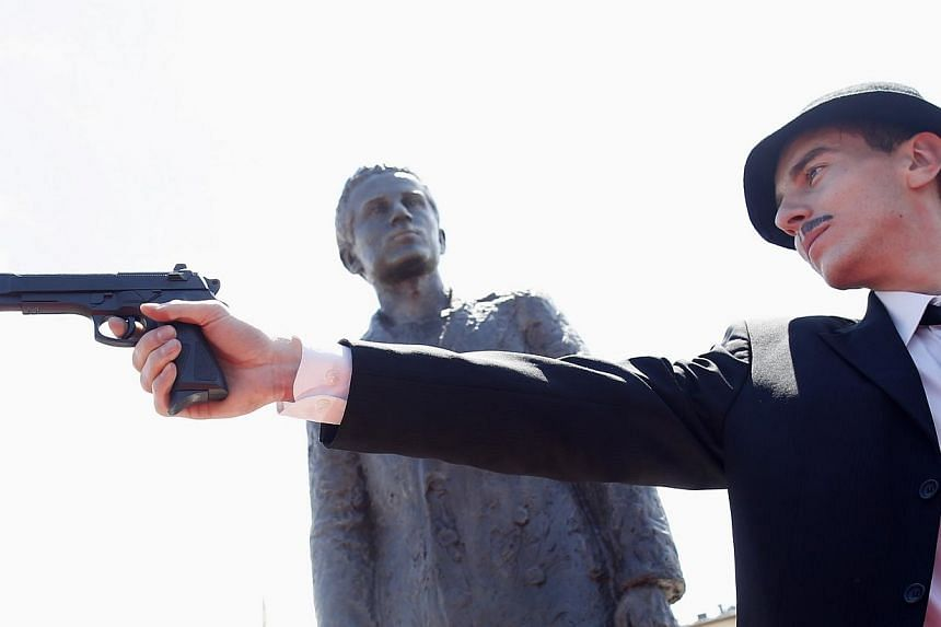 Jovan Mojsilovic, an actor, re-enacts Gavrilo Princip's assassination in front of a statue of Prinsip after it was uncovered during an opening ceremony in East Sarajevo on June 27, 2014.Sarajevo on Saturday, June 28, 2014, marked 100 years sinc