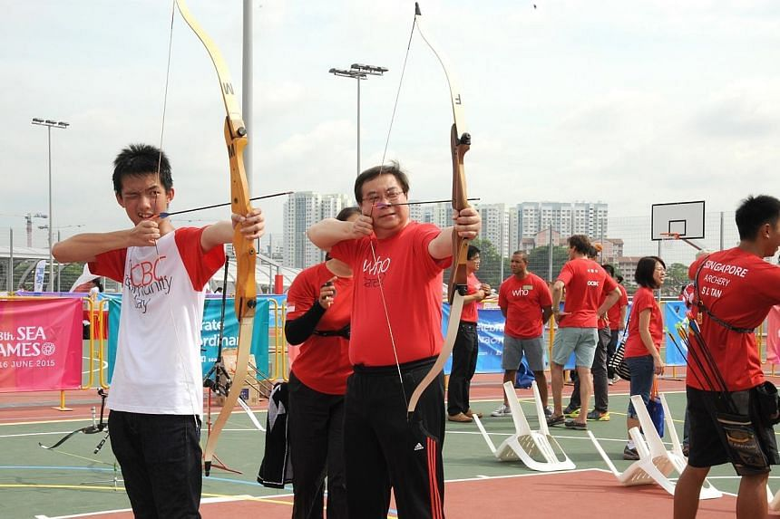 Having a go at the bull's eye – OCBC Group CEO, Mr Samuel Tsien (right), and Mr Jacky Lim from the Singapore Children's Society. -- PHOTO: OCBC