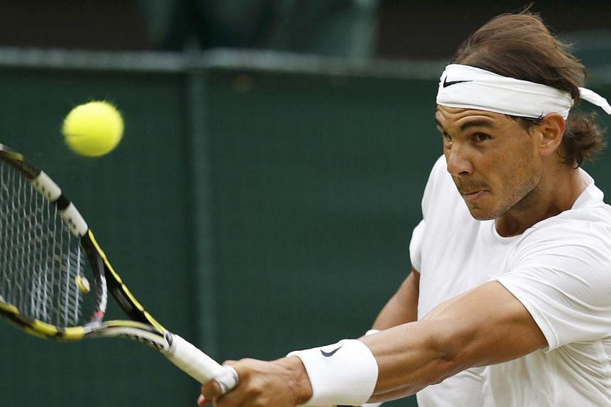 Rafael Nadal of Spain hits a return to Mikhail Kukushkin of Kazakhstan during their men's singles tennis match at the Wimbledon Tennis Championships, in London on June 28, 2014. -- PHOTO: REUTERS