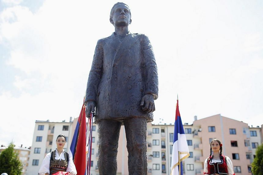 Girls stand next to the Mounument of Gavrilo Princip after an opening ceremony in East Sarajevo on June 27, 2014. -- PHOTO: REUTERS