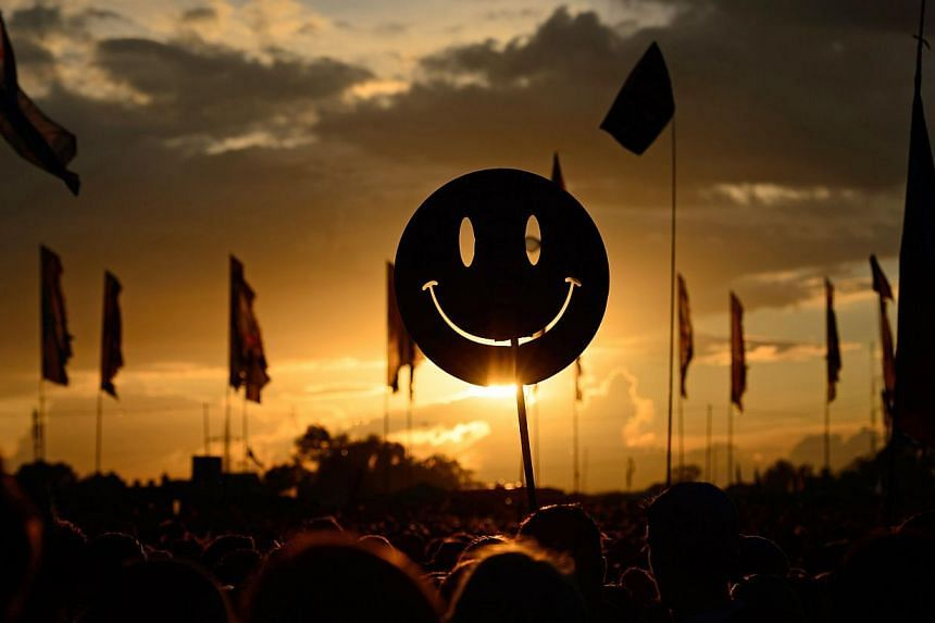 A smiley face sign is carried through the crowds as the sun sets on the first official day of the Glastonbury Festival of Music and Performing Arts in Somerset, south-west England, on June 27, 2014. -- PHOTO: AFP