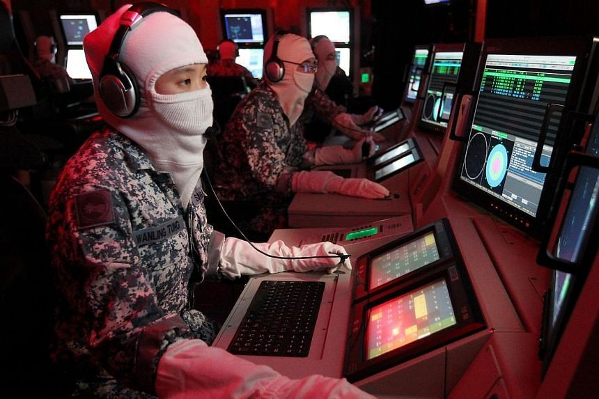 (Left) Captain Tung Wanling and other crew undergo a simulation training in the RSS Formidable's Combat Information Centre. The RSS Formidable has won Best Ship for the second time in the SAF Day Best Unit Competition.-- ST PHOTO: SEAH KWANG PE