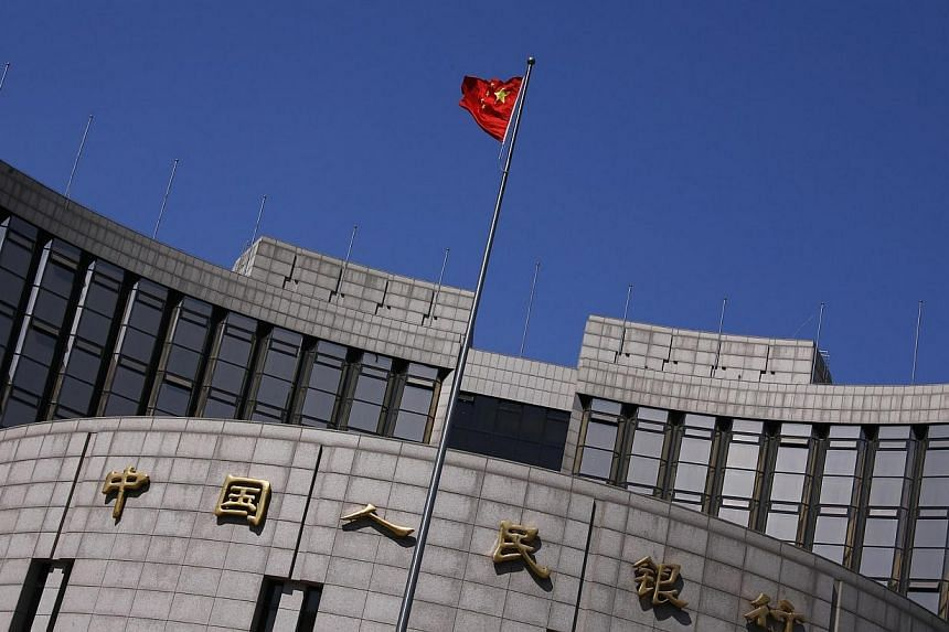 A Chinese national flag flutters outside the headquarters of the People's Bank of China, the Chinese central bank, in Beijing, April 3, 2014. -- PHOTO: REUTERS