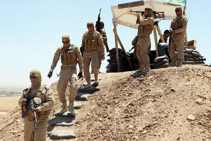 Members of Kurdish security forces take their positions during an intensive security deployment and a patrol looking for militants of the Islamic State in Iraq and Syria (ISIS), on the outskirts of Mosul on June 22, 2014.Iran is ready to help I