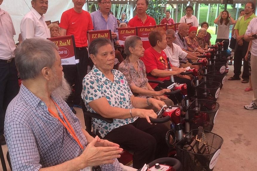Elderly residents try out electric scooters at Radin Mas on June 29. -- ST PHOTO: TOH YONG CHUAN