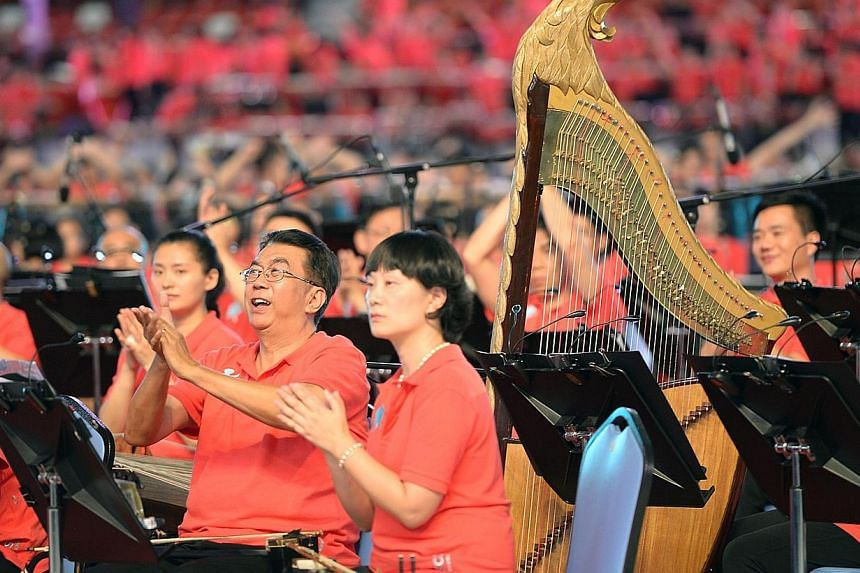 A mass of musicians playing in the new Sports Hub on Saturday, June 28, 2014. -- ST PHOTO: DESMOND WEE