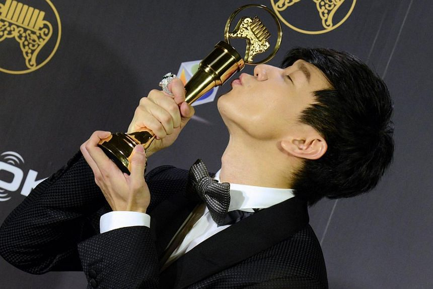 Singaporean singer-songwriter JJ Lin kisses his trophy after winning the Best Mandarin Male Singer award at the 25th Golden Melody Awards in Taipei on June 28, 2014. -- PHOTO: AFP