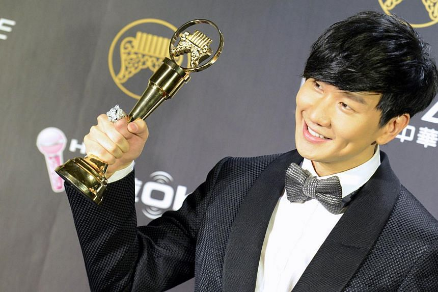 Singaporean singer-songwriter JJ Lin poses for a photograph with a trophy after winning the Best Mandarin Male Singer award at the 25th Golden Melody Awards in Taipei on June 28, 2014. -- PHOTO: AFP