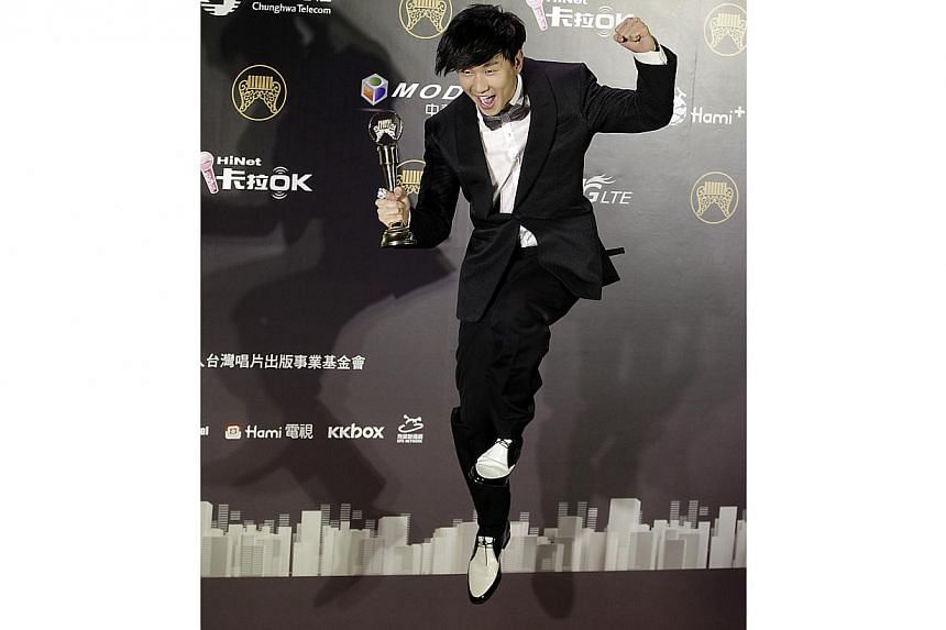 Singaporean singer JJ Lin jumps after winning the Best Mandarin Male Artist award at the 25th Golden Melody Awards in Taipei on June 28, 2014. -- PHOTO: REUTERS