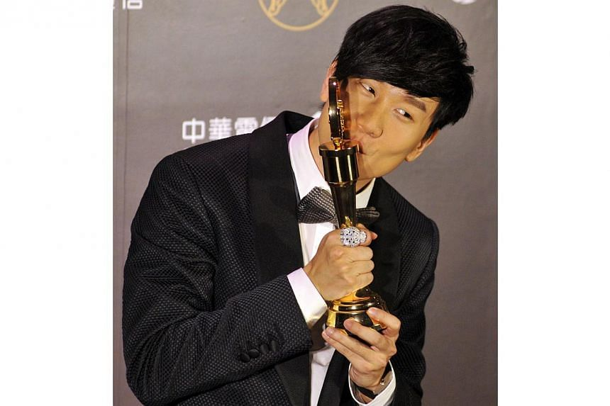 Singaporean singer-songwriter JJ Lin kisses his trophy after winning the Best Mandarin Male Singer at the 25th Golden Melody Awards in Taipei on June 28, 2014. -- PHOTO: AFP