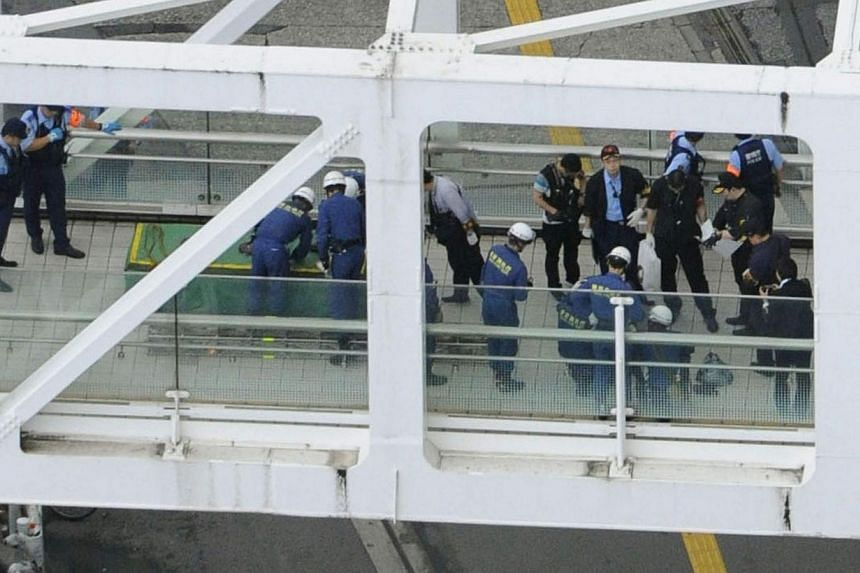 Police officers and firefighters investigating the site where a man set himself on fire at a pedestrian walkway near Shinjuku station in Tokyo, in this photo taken by Kyodo on June 29, 2014. The man set himself on fire at a busy intersection in Tokyo