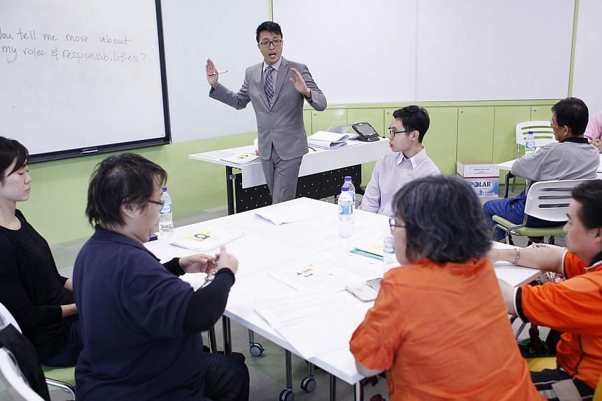 A trainer with SG Enable, Rupert Gan, 35 (centre) speaks to participants of a training workshop at the Lifelong Learning Institute on 25 June, 2014. Such training workshops for disabled job seekers are organised by SG Enable and they cover topics suc