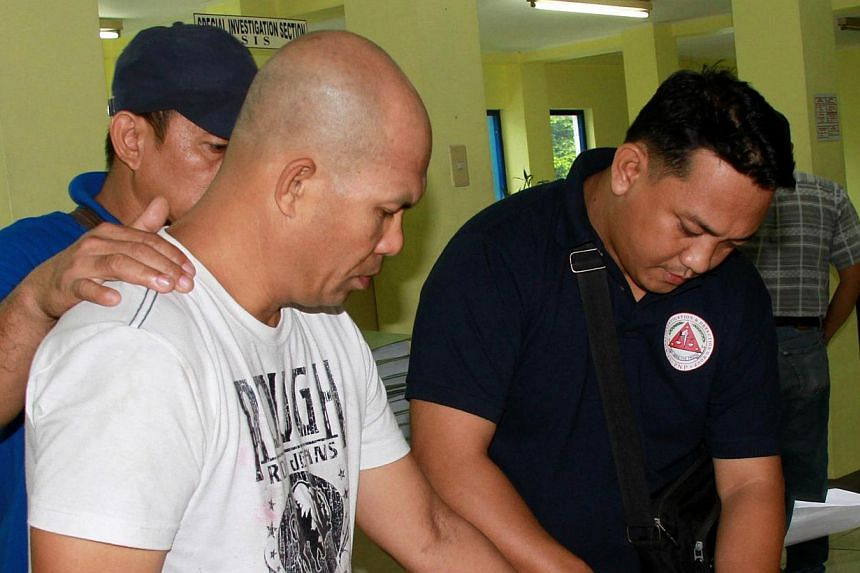 This handout photo taken on June 11, 2014 and released by the Philippine National Police shows senior Philippine Islamic militant Khair Mundos (front L) being fingerprinted by Philippine police after he was arrested in Manila following a manhunt last