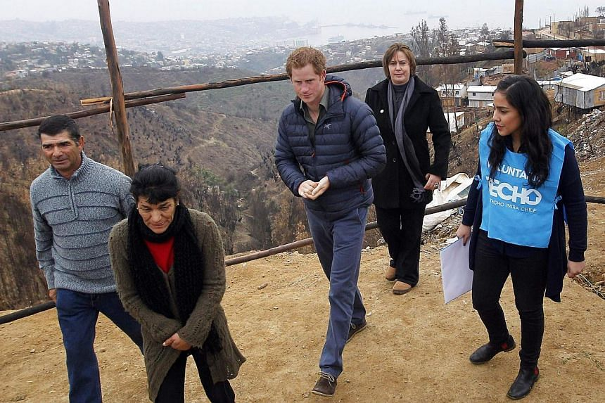 Britain's Prince Harry (centre) walks with members of the non-governmental organization TECHO as he tours El Vergel neighbourhood in Valparaiso city on June 28, 2014. -- PHOTO: REUTERS