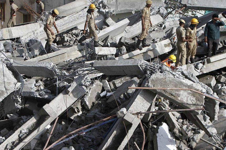 Rescue workers conduct a search operation for survivors at the site of a collapsed 11-storey building that was under construction on the outskirts of the southern Indian city of Chennai on June 29, 2014. Rescuers searched desperately for survivo