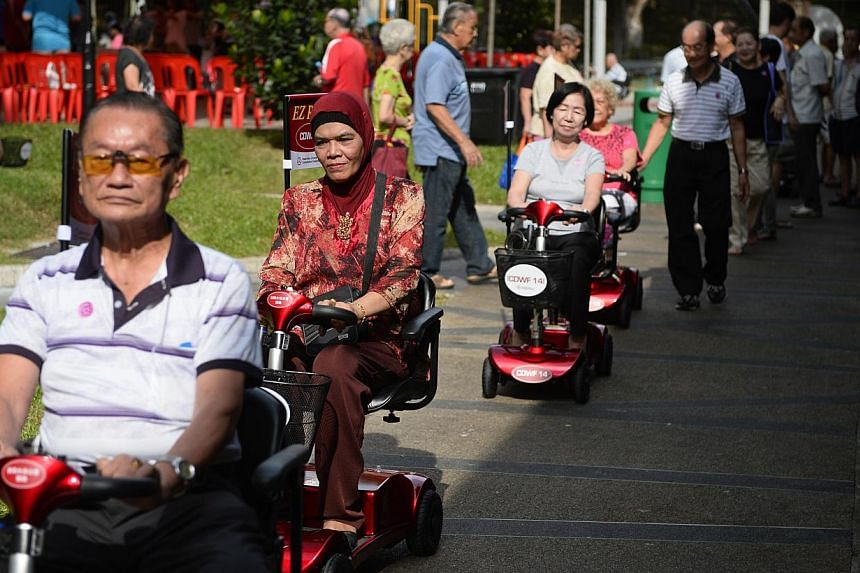 Elderly folk living in Radin Mas SMC test out the scooters around the Blk 11 Telok Blangah Crescent Food Centre after the launch of Radin Mas EZ Roam on June 29, 2014.-- ST PHOTO:MARK CHEONG