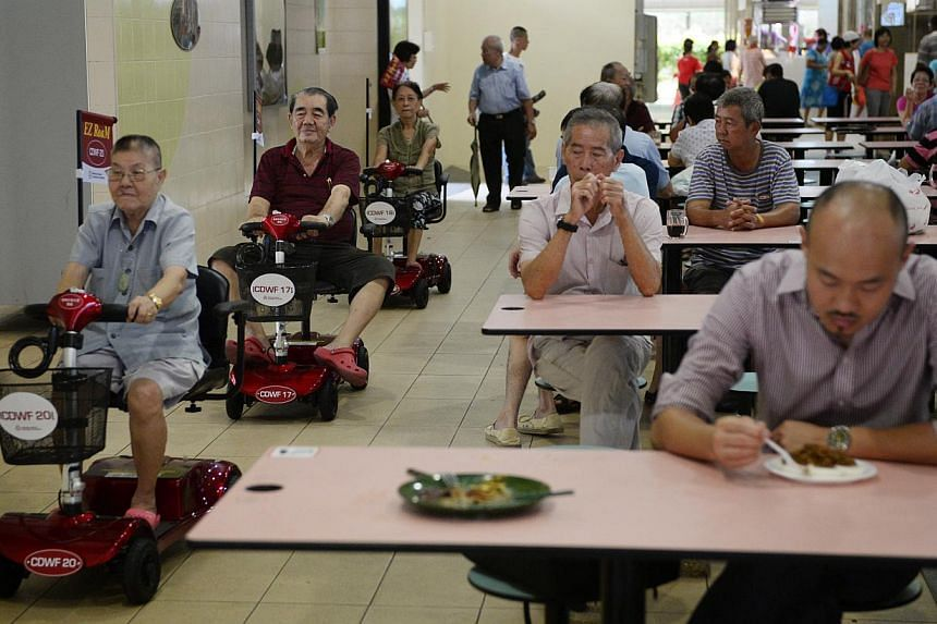 Elderly folk (left) living in Radin Mas SMC test out the scooters around the Blk 11 Telok Blangah Crescent Food Centre after the launch of Radin Mas EZ Roam on June 29, 2014.-- ST PHOTO:MARK CHEONG