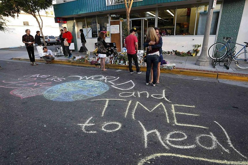 """Women hug next to a chalk message that reads """"World give us love and time to heal"""" outside a deli that was one of nine crime scenes after series of drive-by shootings that left seven people dead in the Isla Vista neighbourhood of Santa Barbara, Calif"""