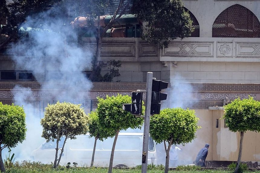 People run for cover moments after a bomb blast in the vicinity of the Ittihadiya palace in the Egyptian capital Cairo, on June 30, 2014.Two Egyptian police officers were killed defusing bombs near the presidential palace in Cairo on Monday, al