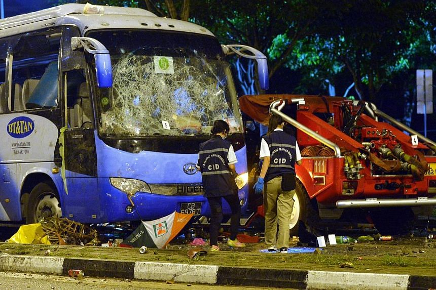 Police officers examining the wrecked private bus at the aftermath of the Little India riot in the early hours on 9 December 2013. -- ST PHOTO: ALPHONSUS CHERN