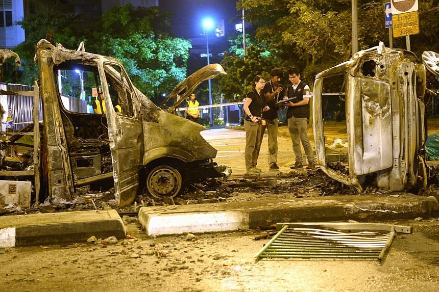 Police officers examining an ambulance and a police car that were burnt beyond recognition along Race Course Road at the aftermath of the Little India riot in 8 December 2013. -- ST PHOTO: DESMOND WEE