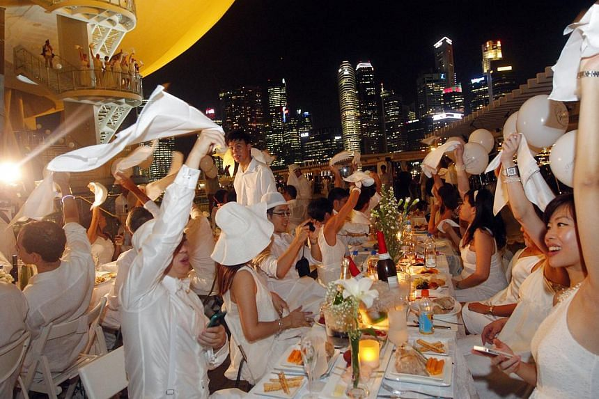 People at the Diner en Blanc or White Dinner held at the ArtScience Museum at Marina Bay Sands on 30 August 2012. -- PHOTO: ST FILE