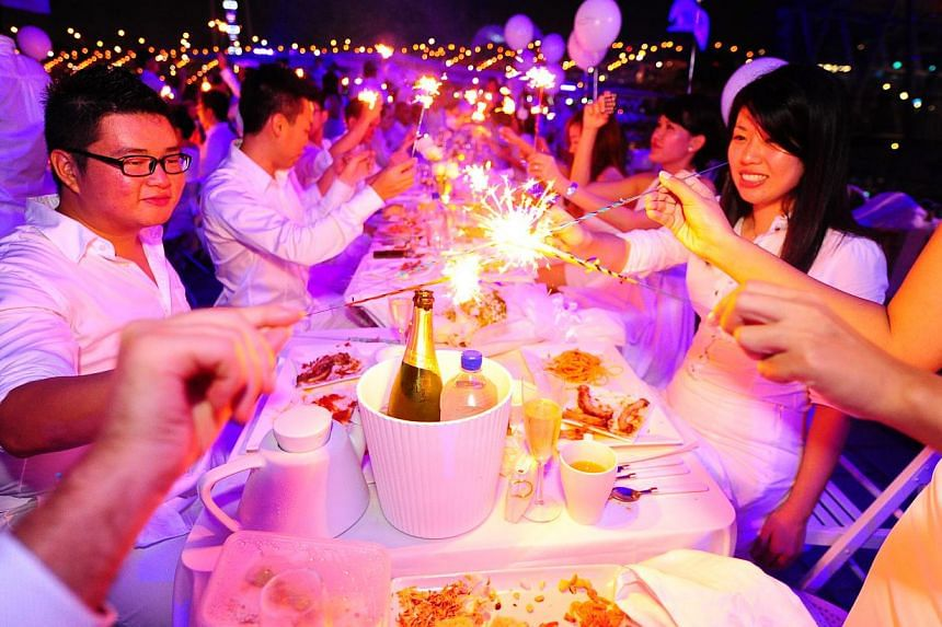 Some of the invitees having a great time at the Diner en Blanc or The White Dinner. -- PHOTO: ST FILE