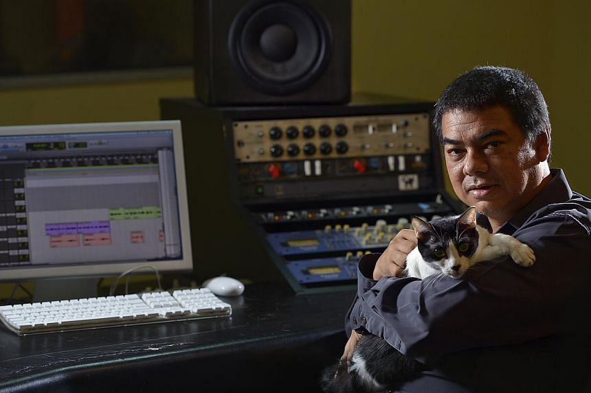 Snakeweed Studios owner Leonard Soosay with one of the three cats in the studio. The animal lover took in four strays, with one at home. -- ST PHOTO: DESMOND WEE