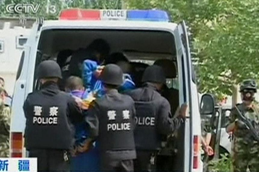 Riot policemen lead men who are about to be executed into a police van in this still image taken from video in an unknown location in the Xinjiang Uighur Autonomous Region, June 16, 2014. Courts in China's western Xinjiang region have sentenced 113 p