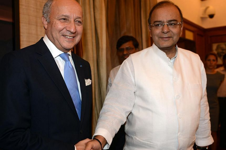French Foreign Minister Laurent Fabius (L) and Indian Defence and Finance Minister Arun Jaitley shake hands during a meeting in New Delhi on June 30, 2014. Fabius is in India for a two-day official visit during which India and France are expected to