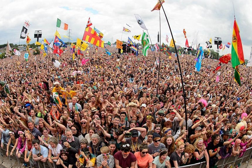 Fans enjoy the music as US singer Dolly Parton performs on the Pyramid Stage, on the final day of the Glastonbury Festival of Music and Performing Arts on Worthy Farm in Somerset, south-west England, on June 29, 2014.  -- PHOTO: AFP
