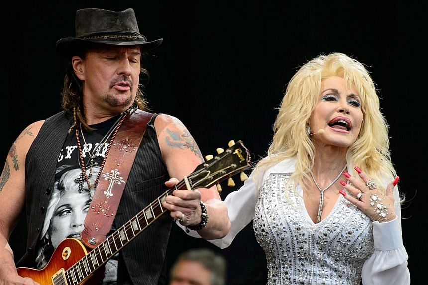Richie Sambora of US rock group Bon Jovi joins US singer Dolly Parton on the Pyramid Stage, on the final day of the Glastonbury Festival of Music and Performing Arts on Worthy Farm in Somerset, south-west England, on June 29, 2014. -- PHOTO: AFP