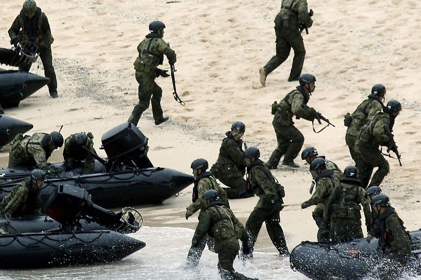 Japan Self-Defense Force (JSDF) soldiers land on Eniyabanare Island during a military drill, off Setouchi town on the southern Japanese island of Amami Oshima, Kagoshima prefecture, in this photo taken by Kyodo May 22, 2014. -- PHOTO: REUTERS